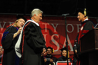 NWA Media/ANDY SHUPE - Gov. Mike Beebe, center, smiles as Sharon Gaber, provost and vice chancellor for academic affairs at the University of Arkansas, left, and  Jim von Gremp, chairman of the university's Board of Trustees, right, bestow upon him an an honorary degree during fall commencement exercises Saturday, Dec. 20, 2014, at Barnhill Arena on the university campus in Fayetteville.