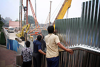"""CHINA. Beijing. A man peer over a fence, watching construction in southern Beijing. In recent years construction has boomed in Beijing as a result of the country's widespread economic growth and the awarding of the 2008 Summer Olympics to the city. For Beijing's residents however, it seems as their city is continually under construction with old neighborhoods regularly being razed and new apartments, office blocks and sports venues appearing in their place. A new Beijing has been promised to the people to act as a showcase to the world for the 'new' China. Beijing's residents have been waiting for this promised change for years and are still waiting, asking the question """"Where's the new Beijing?!"""". 2008."""