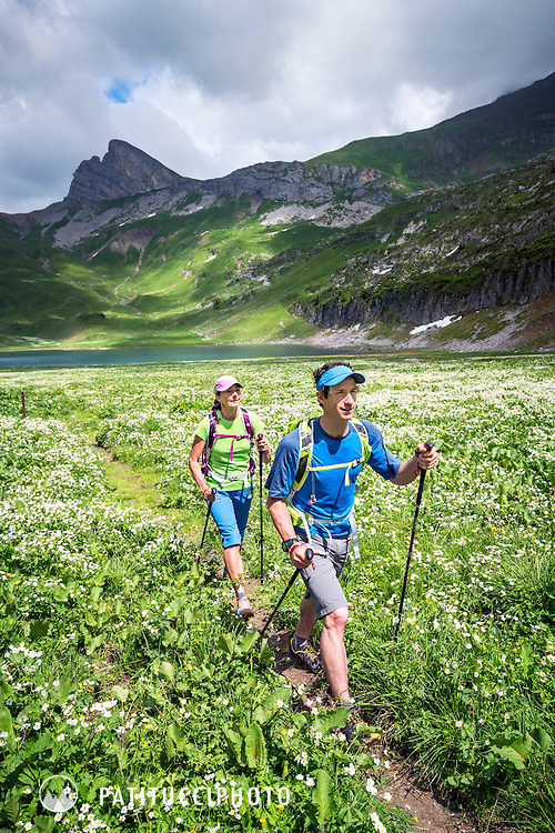 A couple hiking through a flower filled green landscape in the Swiss Alps between Grindelwald and Interlaken, Switzerland