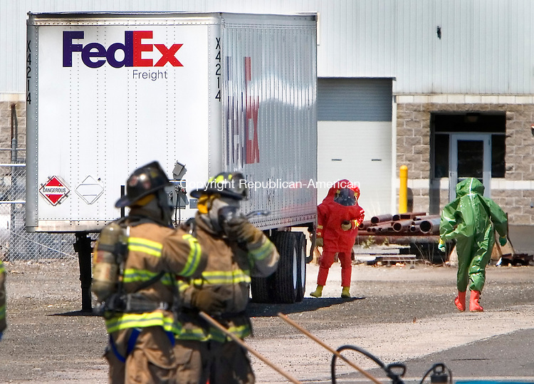 WATERBURY, CT. 06 May 2010-050610SV02--Waterbury firefighters from the Haz-Mat team made entry into a FedEX tractor trailer that was leaking it cargo on South Leonard Street in Waterbury Thursday. The truck was carrying 12-55 gallon drums with Hydrogen Peroxide 24%, Nitric Acid 15%, and Acetic Acid 23%.  Steven Valenti Republican-American