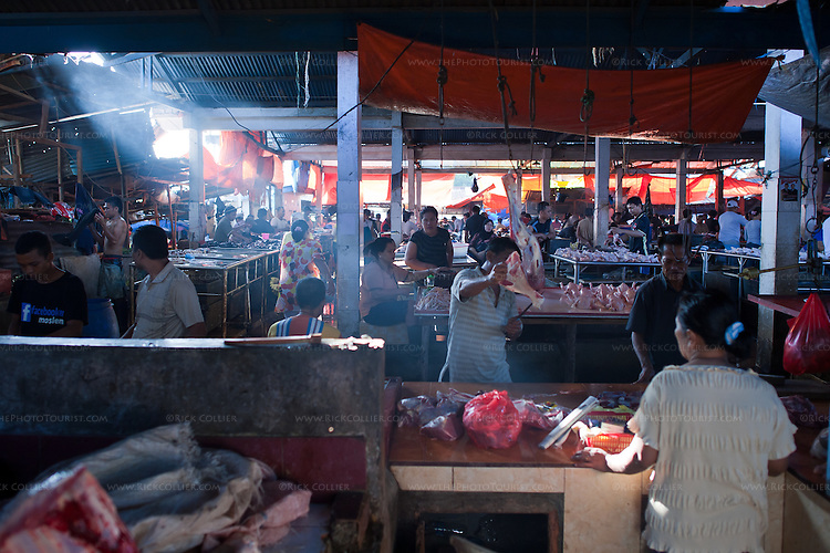 A beam of sunlight illuminates the butcher's work surface in Aertembaga Market (Bitung, North Sulawesi, Indonesia).