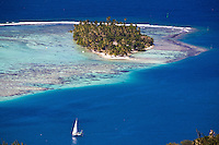 Yacht sailing into pass with sandy islet on Raiatea, Tahiti