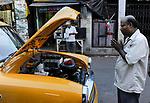 INDIA Kolkata Calcutta , owner and taxi driver pray for his new  HM Ambassador yellow cab at Kali Ghat / INDIEN Kolkata Kalkutta , Taxifahrer und Autobesitzer spricht ein Gebet am Kali Ghat fuer sein neues Ambassador Taxi nachdem ein Hindu Priester es geweiht hat, der HM Ambassador laeuft heute noch neu nach Vorlage des Oxford Morris bei HM Hindustan Motors vom Band