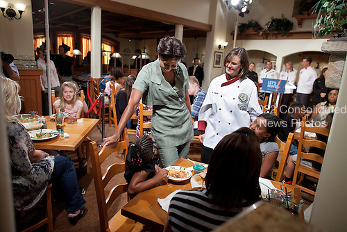 First Lady Michelle Obama and Darden Restaurants chef Julie Elkinton greet diners following an event at an Olive Garden restaurant in Hyattsville, Maryland, September 15, 2011. The First Lady joined Darden Restaurants and Partnership for a Healthier America to announce the company's committment to reduce its calorie and sodium footprints, and to provide greater choice and variety to families through changes to its kids' menus. .Mandatory Credit: Chuck Kennedy - White House via CNP