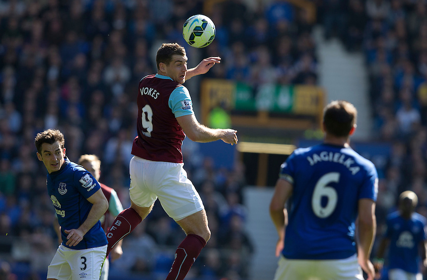 Burnley's Sam Vokes jumps to head the ball between Everton's Leighton Baines and Phil Jagielka<br /> <br /> Photographer Stephen White/CameraSport<br /> <br /> Football - Barclays Premiership - Everton v Burnley - Saturday 18th April 2015 - Goodison Park - Everton<br /> <br /> &copy; CameraSport - 43 Linden Ave. Countesthorpe. Leicester. England. LE8 5PG - Tel: +44 (0) 116 277 4147 - admin@camerasport.com - www.camerasport.com