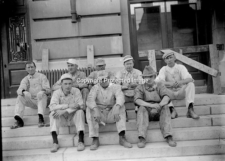 BUILDING CREW AT THE POST OFFICE, C. 1915. Eight workmen--probably painters--sit for a portrait on the east, main steps of the post office during the construction of 1915-1916. That project extended the original post office and rearranged much of the ground floor of the 1905 building. The lobby today retains marble wainscoting and oak trim from 1905, but in positions to which those fine finishes were relocated in 1915.<br />