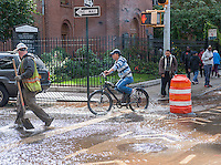 Bicyclists maneuver through flowing water from a watermain break  in the Chelsea neighborhood of New York on Wednesday, October 12, 2016. The watermain break caused water to gush but it was mostly contained to the street safely running into storm drains. (© Richard B. Levine)