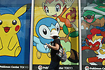 """May 9, 2010 - Tokyo, Japan - A Japanese woman plays Nintendo's portable video game 'DS' in front of the official Pokemon store in Tokyo on May 9, 2010. Nintendo recently announced that the DS handheld device had become the best selling gaming handheld of all time, with a total of 129 million units sold. The DS 'family' have surpassed the """"Game Boy"""" series which hit 118 million over two decades."""