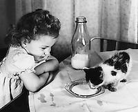 Young girl feeding the kitten milk.