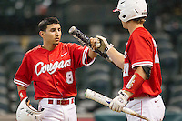 Houston Cougar second baseman Josh Vidales #8 is greeted by teammate Caleb Barker #27 after scoring against the Texas A&M Aggies in the NCAA baseball game on March 1st, 2013 at Minute Maid Park in Houston, Texas. Houston defeated Texas A&M 7-6. (Andrew Woolley/Four Seam Images).