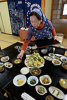 A member of staff at the Ashiya guesthouse setting out a meal of cooked mountain vegetables. Tsuruoka, Yamagata Prefecture, Japan, April 9, 2016. The city of Tsuruoka in Yamagata Prefecture is famous for its sansai mountain vegetable cuisine. These foraged grasses, fungi and vegetables are also used by the mountain ascetics of the Shugendo religion.