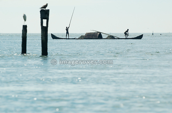India, Kerala, Backwaters. Working indian men on their boat (punt) in the backwaters between Kollam to Allepey. No releases available.
