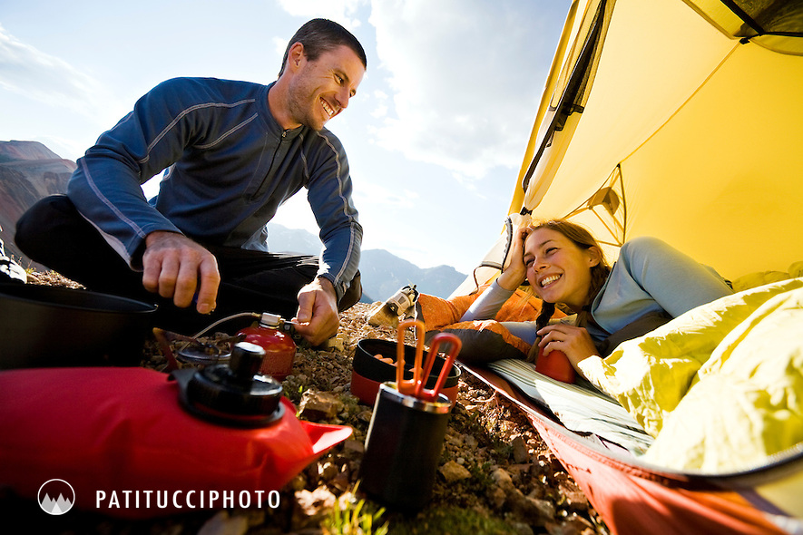 Gabriel Luethje and Blaque Reily-Orth in their backpacking camp while backpacking in the San Juans. She is inside the tent in her sleeping bag while he sits outside with the campstove