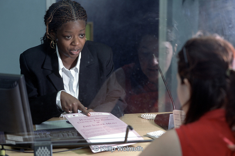 Protected by a glass screen, a member of staff gives advice on Housing Benefit to a local resident at Bethnal Green One Stop Shop, Tower Hamlets, London.