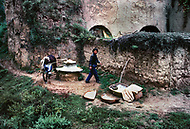 September, 1985. Shaanxi Province, China. The caves of Yan'an are more than 500 years old and still provide shelter for the farmers. Behind that man a donkey grinds grain to make rice flour.