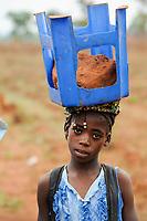 ANGOLA Kwanza Sul, village Kassombo, children on way to school, each child must bring his own plastic chair as the schools in poor condition due to the civil war and corruption, the revenues from oil rich Angola seems not reach the villages / ANGOLA Kwanza Sul, Dorf Kassombo, Kinder mit Plastikstuehlen auf dem Weg zur Schule durch Felder des Dorfes, da die Schulen durch den Buergerkrieg zerstoert und ohne Inventar sind, muss jedes Kind seinen Plastik Stuhl mitbringen