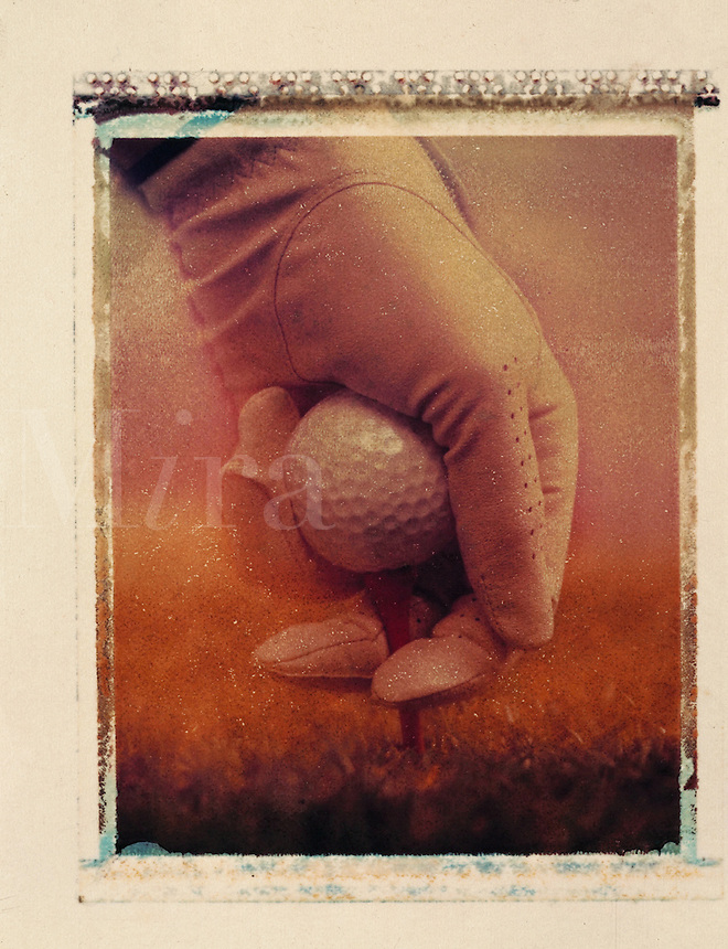 Sepia tone image of a gloved hand holding a golf ball.