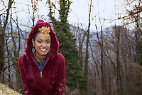 Switzerland. Canton Ticino. Aranno. Orpheline stands in the garden of her home. Orpheline is a composer, song writer, a singer and a musician. She is a young woman (24 years old). Her mother is swiss and her father was a black american citizen. Mixed race. Aranno is located in the Malcantone area. 19.03.2010 © 2010 Didier Ruef