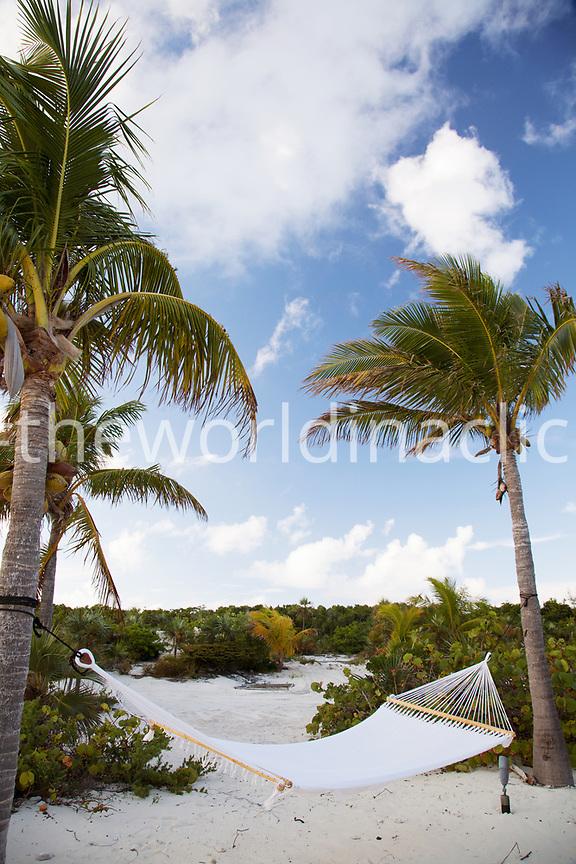 EXUMA, Bahamas. A Hammock along the beach at the Fowl Cay Resort.