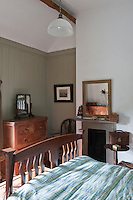 The master bedroom is partly panelled in traditional tongue-and-groove painted a warm grey-green and furnished with wooden pieces