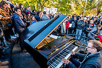 New York, NY - 14 November 2015 NYC  Classical pianist Colin Huggins plays piano during a vigil in Washington Square Park to commemorate the victims of the 13 November Paris terror attacks.