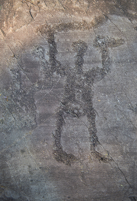 Petroglyph, rock carving, of a warrior with a sword and shield. Carved by the ancient Camunni people in the iron age between 1000-1200 BC. Rock 22, Foppi di Nadro, Riserva Naturale Incisioni Rupestri di Ceto, Cimbergo e Paspardo, Capo di Ponti, Valcamonica (Val Camonica), Lombardy plain, Italy