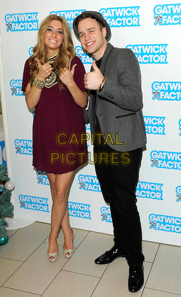 "STACEY SOLOMON & OLLY MURS .X Factor 2009 Finalists launch ""The Gatwick Factor"", helping raise money for Great Ormand Street hospital. .Gatwick Airport, London, England, UK, .16th December 2009..photocall full length  grey gray jacket black trousers hat maroon jumper sweater purple dress gold bracelet  cuff smiling black patterned pattern thumbs up gesture peep toe shoes .CAP/FIN.©Steve Finn/Capital Pictures."