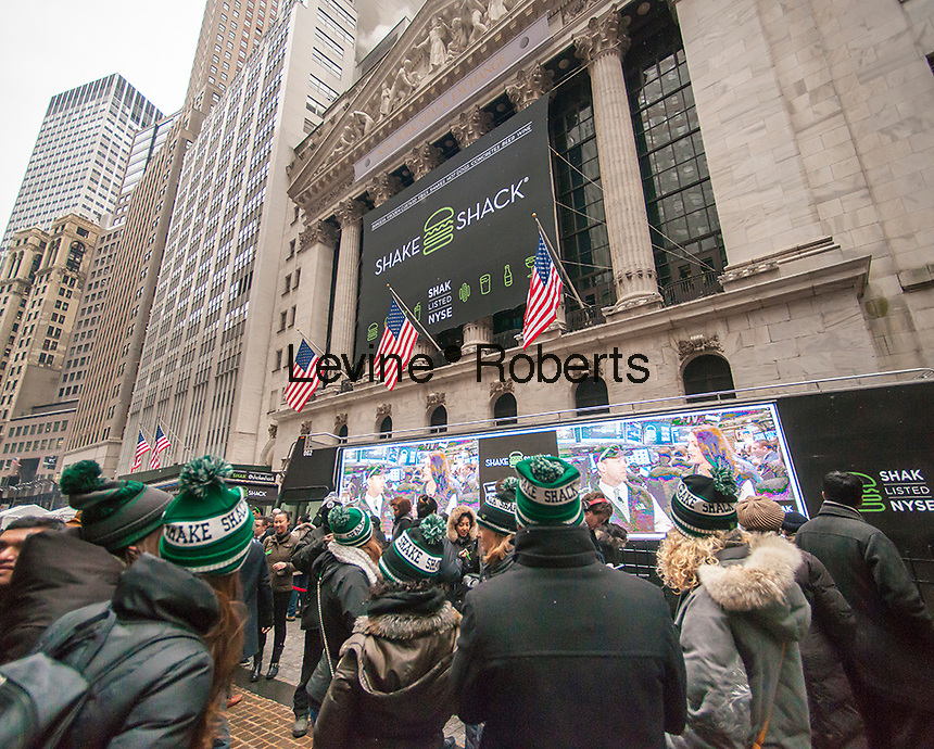 Crowds of burger lovers line up for free burgers outside the New York Stock Exchange decorated for the Shake Shack's first day of trading on their Initial Public Offering on Friday, January 30, 2015. The stock of the burger joint more than doubled so far after opening at $47 per share valuing the company at over $1 billion. The restaurant has 63 worldwide locations and started out in 2001 as a hot dog stand in Madison Square Park.(© Richard B. Levine)
