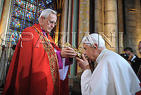 Pope Benedict XVI holds a cross as he celebrates a vespers service in Notre-Dame cathedral in Paris Friday, Sept. 12, 2008.