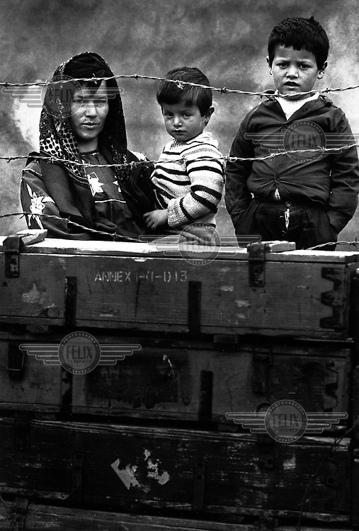 MAWAT, KURDISTAN, IRAQ, MARCH 1994. A Kurdish family stands behind their fence of recicled war material. Twenty million landmines and unexploded ordnance litter the former frontline in the Iran vs Iraq War still killing and maim ing Kurdish people on a daily basis.©Photo by Frits Meyst/Panos Pictures
