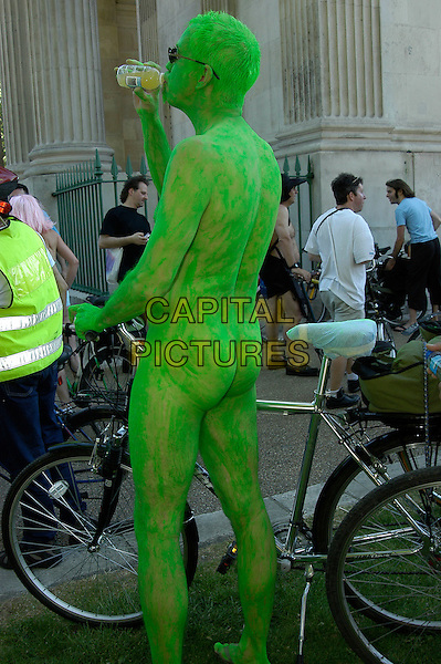 PARTICIPANT.People Taking part in the 3rd World Naked Bike Ride (& Skate) Protest Against Oil Dependency, starting and finishing at Wellington Arch, Hyde Park, London, 10th June 2006..Full length skin nude nudist bike bicycle painted body paint green bum back behind drinking.Ref: IA.www.capitalpictures.com.sales@capitalpictures.com.©Ian Allis/Capital Pictures