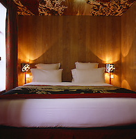The walls of this compact bedroom are covered in wood panels and the ceiling is wallpapered