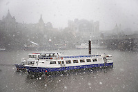 Boat on the River Thames London with large snow flakes falling - winter scene