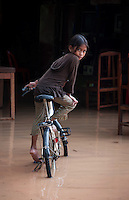A village that is flooded during the Monsoon Season near the Tonle Sap Lake, Cambodia A local pretty Khmer girl on her bike in the flooded street and home