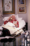 elderly woman lying in home hospital bed talking on phone while reading get well card