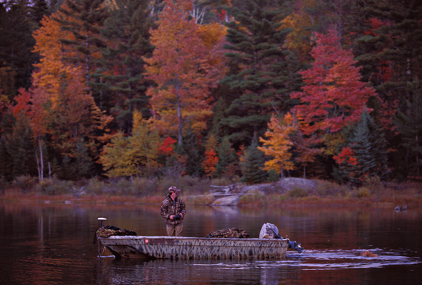 FALL FOLIAGE SURROUNDS A WATERFOWL HUNTER AND HIS CHESAPEAKE BAY RETRIEVER AS THEY PREPARE TO HUNT ON DEER LAKE NEAR ISHPEMING, MICHIGAN.