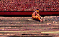 A Buddhist Monk fixing the roof of the Monastery Luang Prabang, Laos