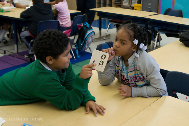 Oakland Ca 2nd graders testing each other on math with flash cards in class