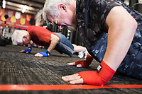 NWA Democrat-Gazette/CHARLIE KAIJO Grant Weatherill of Rogers (foreground) does a pushup during a boxing class, Monday, June 11, 2018 at  Straightright Boxing and Fitness in Springdale.<br />