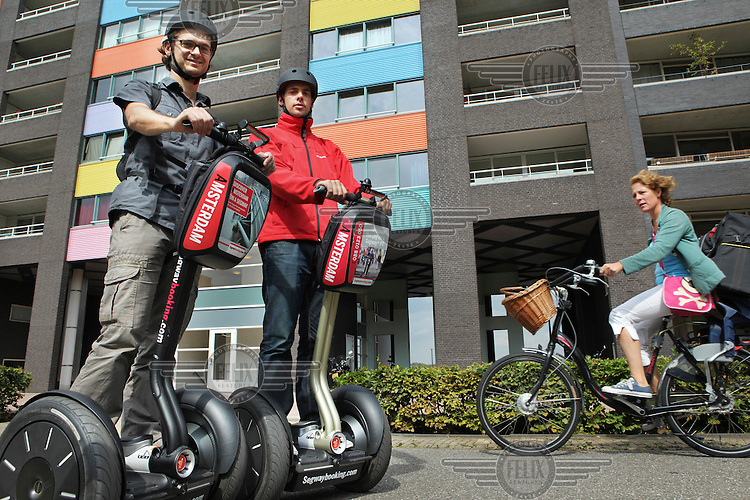 Two men tour Amsterdam by Segway, a two wheeled motorised vehicle.