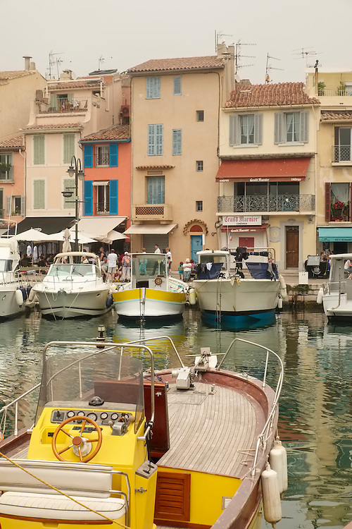 The picturesque port of Cassis contains rows of fishing boats and pastel-colored buildings.