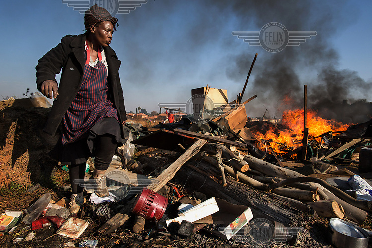 A resident tries to salvage some of her things as the Red Ants evict residents and destroy an informal settlement near Pomona. <br />