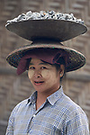 A woman carries gravel on her head as she helps construct a road in Kalay, a town in Myanmar. The woman is wearing thanaka, a cosmetic paste, on her face.