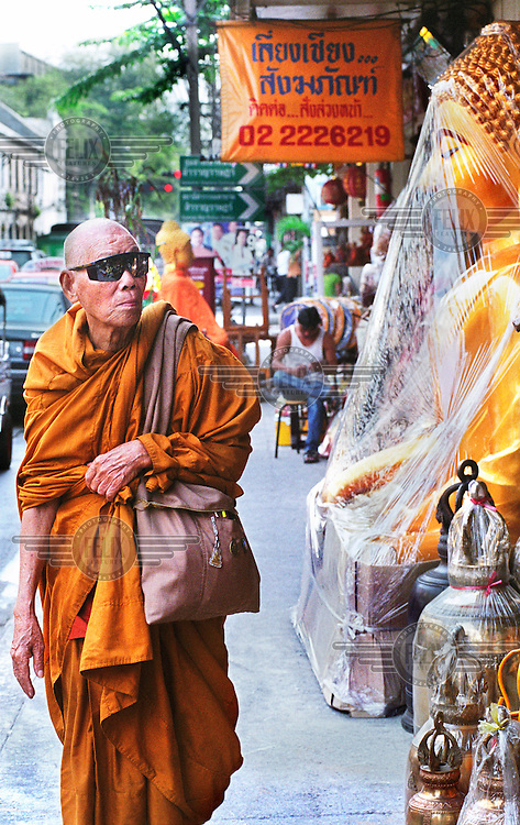 An elderly monk wearing sunglasses walks past a large Buddhist sculpture for sale in the centre of the capital.