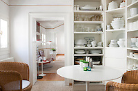 A marble-topped table by Saarinen in a kitchen with open shelving for crockery