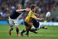 Bernard Foley of Australia offloads the ball after being tackled by John Hardie of Scotland. Rugby World Cup Quarter Final between Australia and Scotland on October 18, 2015 at Twickenham Stadium in London, England. Photo by: Patrick Khachfe / Onside Images
