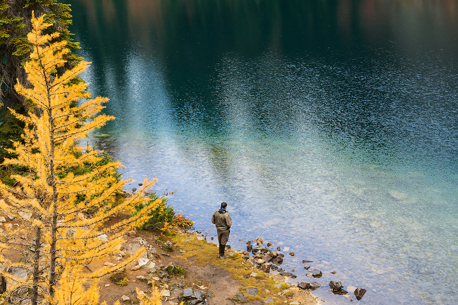 A young man stands on the shore of Blue Lake on a bright, breezy day in Washington's North Cascade mountain range.