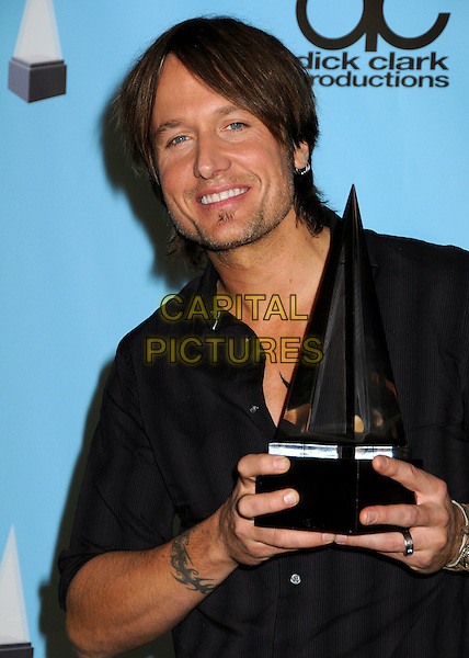 KEITH URBAN .At the 2009 American Music Awards - Press Room held at the Nokia Theatre L.A. Live, Los Angeles, California, USA, .22nd November 2009..AMA AMAs half length black grey gray striped shirt bracelets award trophy soul patch facial hair tattoo .CAP/ADM/BP.©Byron Purvis/AdMedia/Capital Pictures.