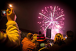 © Joel Goodman - 07973 332324 . 17 November 2013 . Oldham , UK . The crowd watch fireworks over the church . The Christmas lights are turned on in Oldham Town Centre . Photo credit : Joel Goodman