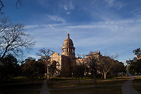 Wide angle view of the Texas State Capitol Building Grounds amid vivid blue skies during a late afternoon sunset.